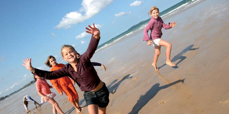 Enfants qui courent sur la plage à marée basse