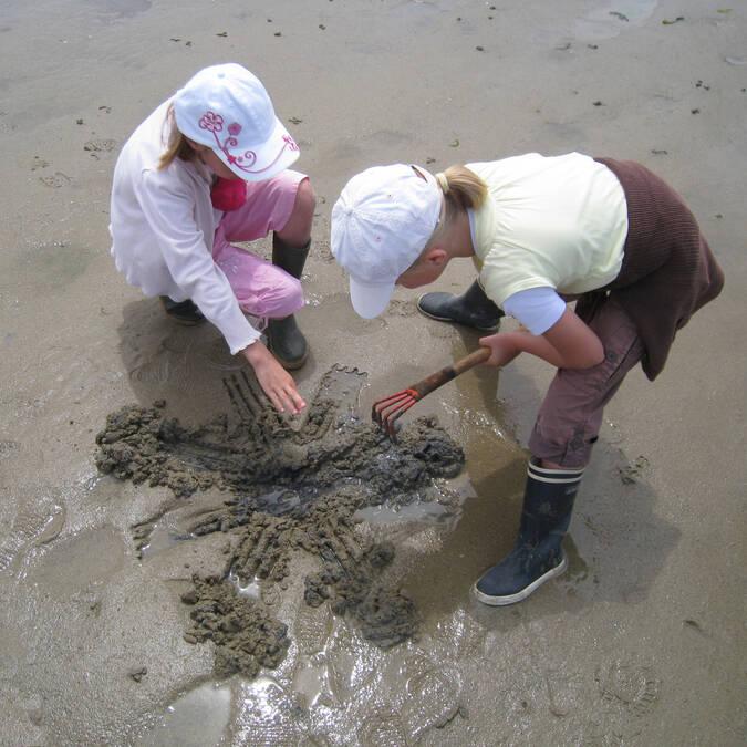 Enfants qui grattent la vase pour pêcher des coquillages